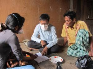 Direct Observed Treatment in a patient's home: MSF Nurse, Village Health Volunteer and a family member discuss the medications