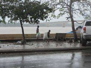 Children scavenging along the embankment during a tropical downpour, yesterday.