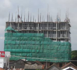 Workers with no hard hats, no harnesses, most in flip-flops, above rooftops in Kampong Cham
